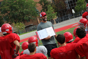 INTRODUCING THE PLAYBOOK: North Toronto CI coach Shawn Hood talks to his charges during an early September practice.
