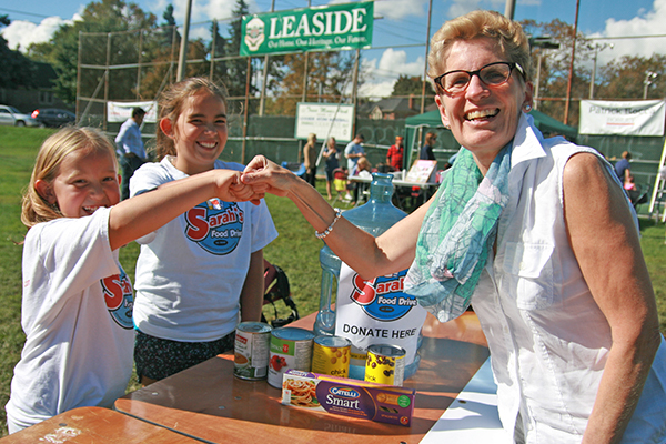 Premier Wynne gives fist bumps of approval to food drive girls in Leaside.