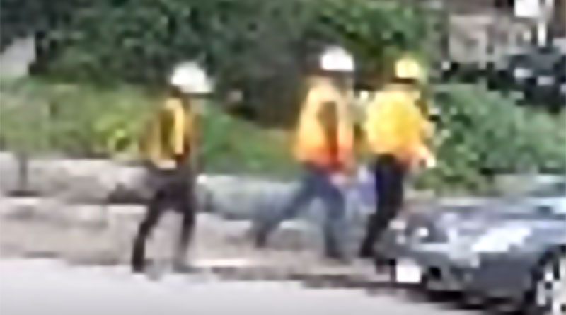 Males in hard hats shown in police video