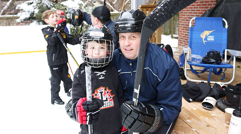 Father and son at backyard rink