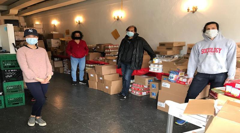 Fort York Food Bank volunteers sort food items into boxes.